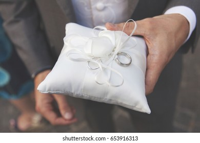 Bestman holding pillow with rings at a wedding ceremony