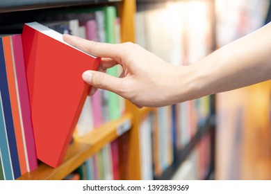 Bestseller publishing concept. Male hand choosing and picking red book from wooden bookshelf in bookstore. Education research in university public library.