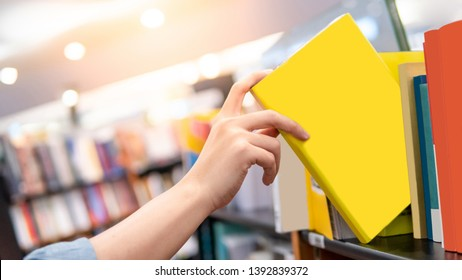 Bestseller publishing concept. Male hand choosing and picking yellow book from wooden bookshelf in bookstore. Education research in university public library.