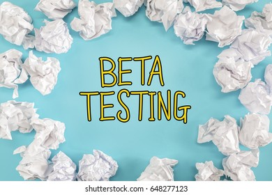 Beta Testing text with crumpled paper balls on a blue background
