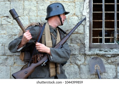 Betchworth Surrey England Oct 1998. An unidentified re-enactor of WW1 wears the period uniform of a German Sturmtrooper a rifle slung on his front he prepares to throw a grenade through a farm window.