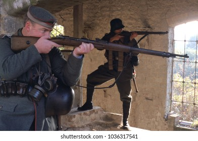 Betchworth Surrey UK Oct 1998. Two unidentified re-enactors of WW1 wear historical uniforms of German shock troops shooting rifles in an old farm building at a re-enactment of Cambrai 1917.