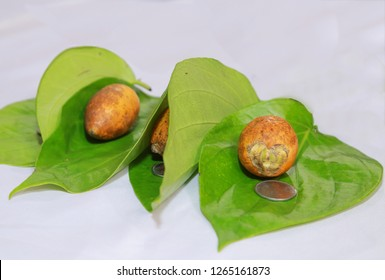 Betel leaves, areca nuts and coins isolated. They are arranged this way as a part of the Hindu marriage custom called Dakshina.