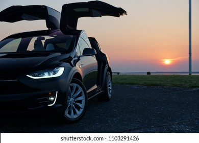Bethany Beach, Delaware / United States - June 10, 2017: Tesla Model X Photoshoot at Bethany Beach Lookout Point with Sunset and Gullwing Doors