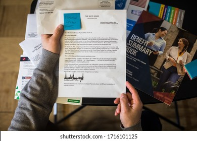Bethesda, Maryland / USA - April 27, 2020: A young American man receives a letter from President Donald J. Trump indicating that his COVID-19 stimulus check has been deposited into his account.