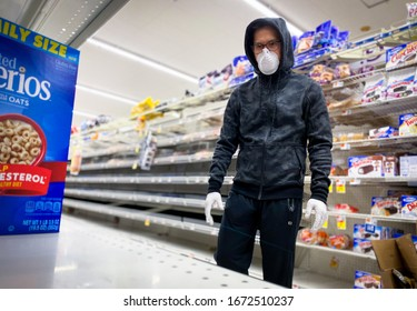 Bethesda, Maryland / USA - March 14, 2020: A man wearing an N95 respirator mask and gloves looks for non perishable foods during the COVID-19 pandemic.