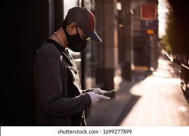 Bethesda, Maryland / USA - March 30, 2020: A young Latino man wearing a protective mask and rubber gloves uses his cell phone to communicate with others during the COVID 19 pandemic.