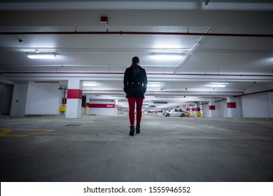 Bethesda, Maryland / USA - Nov. 10, 2019: A young woman with a peacoat and red pants walks alone through a brand new parking garage in downtown Bethesda.
