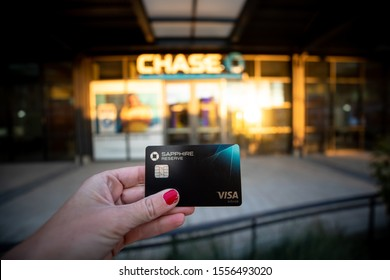 Bethesda, Maryland / USA - Nov. 10, 2019: A woman holds a Chase Sapphire Reserve credit card while standing outside of the bank where she opened it.
