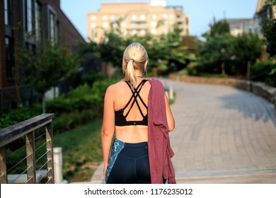 Bethesda, MD - August 12, 2018: A young woman in athletic clothing, including a black sports bra and a pink hoodie, takes a break from running on the sidewalk near the Capital Crescent Trail.