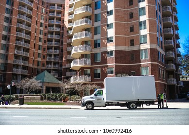 Bethesda, MD - March 31, 2018: An Amazon Prime delivery truck makes a stop outside of a large apartment complex in the downtown Bethesda neighborhood of Montgomery County.