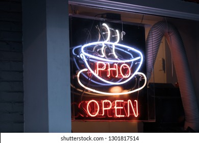 "Bethesda, MD / USA - February 1, 2019: The entrance to Rice Paddies Grill, a Vietnamese noodle soup restaurant, features a neon sign depicting a steaming hot soup and the word ""pho""."