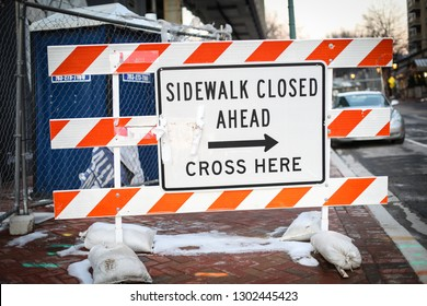 "Bethesda, MD / USA - February 2, 2019: A sidewalk is closed for construction on Bethesda Avenue in Montgomery County. A sign reads: ""Sidewalk closed ahead. Cross here."""
