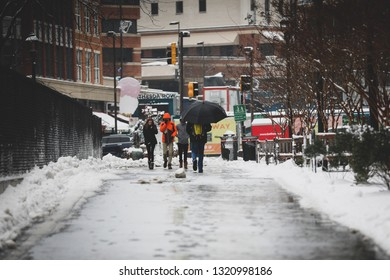 Bethesda, MD / USA - February 20, 2019: A snow day forces many businesses and restaurants to close, but some people brave the cold temperatures and the freezing rain to talk a walk on an icy trail.