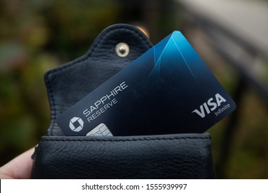 Bethesda, MD / USA - Nov. 10, 2019: A hand holds a Chase Sapphire Reserve credit card, which gives users points towards travel credit and Priority Pass airport lounge access.