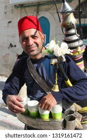 BETHLEHEM, ISRAEL - February 14, 2019. Portrait of a Palestinian man with traditional red fez hat is selling fresh cool drinking water at bazaar in outdoor city street.
