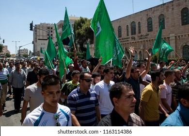 Bethlehem, Palestine, August 1, 2014: Palestinians carry Hamas flags during demonstration against Israel on a street in front of the separation wall in Bethlehem.