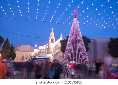 Bethlehem, Palestine - December 24 2017: People gathers at manger Square with a giant Christmas tree to celebrate the Christmas Eve.