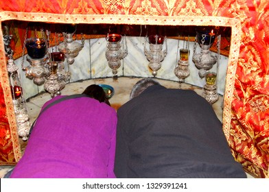 BETHLEHEM, PALESTINE - February 14, 2019. Man and woman couple are praying together and worshiping at the birthplace and the place of the crib where Jesus is born, in the Nativity church.