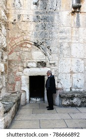 BETHLEHEM, PALESTINE - JANUARY 2, 2011: A man standing next to a very low door, called the Door of Humility, main entrance into the Church of the Nativity