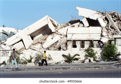 BETHLEHEM, PALESTINIAN AREAS - MAY 26: Two Palestinian boys walk past Palestinian Authority buildings which were bombed to rubble by Israeli fighter jets May 26, 2002 in Bethlehem.