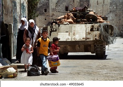 BETHLEHEM, PALESTINIAN AREAS - MAY 28: Palestinian residents of Bethlehem walk near an Israeli tank guarding Manger Square during a lull in curfew imposed by the Israeli military May 28, 2002 in Bethlehem.