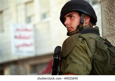 BETHLEHEM, PALESTINIAN AREAS - MAY 28: A soldier of the Israeli Defense Forces patrols the West Bank town of Bethlehem during a curfew imposed on its Palestinian residents May 28, 2002 in Bethlehem.