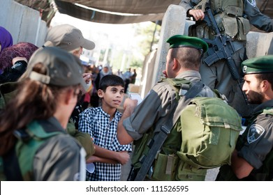 BETHLEHEM, PALESTINIAN TERRITORIES - AUGUST 17: The Israeli military checks a Palestinian boy's papers as he seeks access to Jerusalem through the Bethlehem checkpoint, West Bank, August 17, 2012.