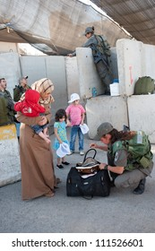 BETHLEHEM, PALESTINIAN TERRITORIES - AUGUST 17: Israeli soldiers check Palestinian women and children at the Bethlehem checkpoint on the last Friday of Ramadan, West Bank, August 17, 2012.