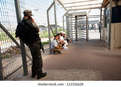 BETHLEHEM, PALESTINIAN TERRITORIES - AUGUST 17: An Israeli soldier detains Palestinians at the Bethlehem checkpoint to Jerusalem on the last Friday of Ramadan, West Bank, August 17, 2012.
