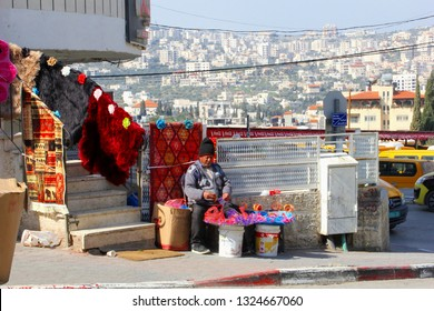 BETHLEHEM, PALESTINIAN TERRITORIES - February 14, 2019. Arabic man is selling carpets, filling bags with sweets and lollies to sell in the street. At the background panoramic view of Bethlehem town.