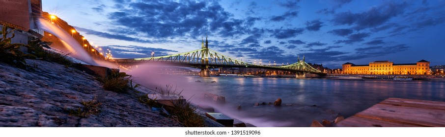 Beton project, a drainage pipe from Szent Gellért Spa which diverts thermal water into Danube and panoramic view of Liberty Bridge, Budapest, Hungary