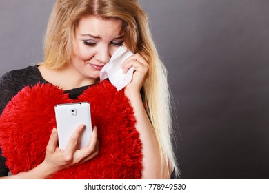 Betrayal, bad relationship, hurt love concept. Sad heartbroken woman crying and looking at her phone.