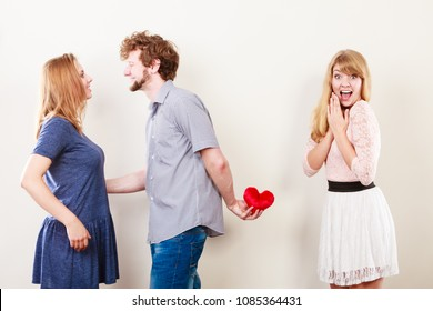 Betrayal and infidelity concept. Handsome boy with two attractive blondie girls. Man cheating women by mislead chosen one and offer his heart to another.