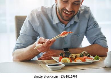 Better food, better mood. Cropped image of smiling handsome businessman eating sushi