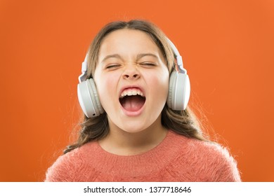 For better vocal performances. Adorable small child doing vocal on song. Little girl listening to music and singing vocal melody. Talented singer or vocalist training her vocal in wireless headphones.