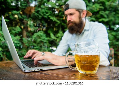 Betting and real money gaming. Brutal man leisure with beer and sport game. Fan bet online championship while sit terrace outdoors with beer. Football fan bearded hipster make bet sport game laptop.