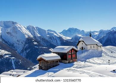 Bettmeralp, Switzerland - February 16. 2019: Chapel Maria in Snow (Kapelle zum Schnee) with two old chalets - the landmark architecture in the Swiss alps village Bettmeralp in Canton Vaud.