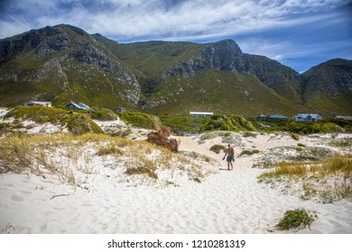 Betty's Bay, Western Cape province/  South Africa - 12.28.2017: White sand on  Overberg coast of South Africa, Betty's Bay.  The man goes to the sea