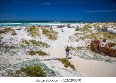 Betty's Bay, Western Cape province/  South Africa - 12.28.2017: White sand on  Overberg coast of South Africa, Betty's Bay. The girl running to the sea