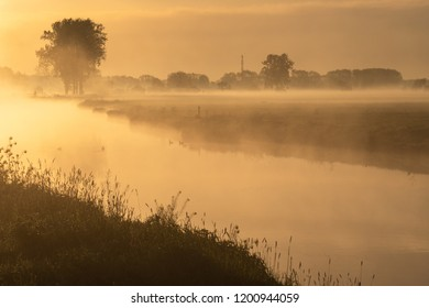 Betuwe, Gelderland, the Netherlands - May 3, 2018 : A small river with mist on an early morning in the Betuwe