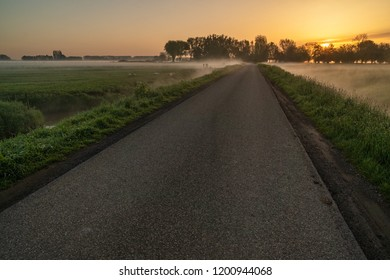 Betuwe, Gelderland, the Netherlands - May 3, 2018 : Local road through the grass fields in the Betuwe at sunrise