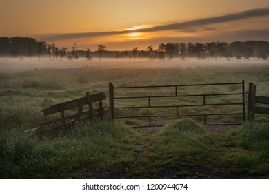Betuwe, Gelderland, the Netherlands - May 3, 2018 : Fence from a misty grass field in the Betuwe