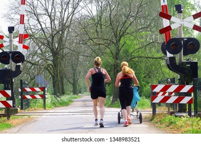 BETUWE, NETHERLANDS - April 21, 2018. Two young Dutch women with baby in buggy are jogging together at a forest road near a railway crossing.