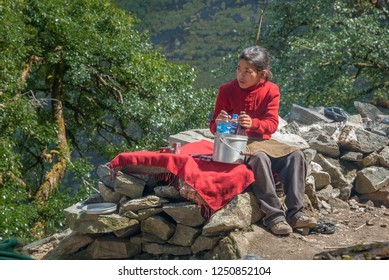 Between Chame and Danagyu villages, Around Annapurna trek, Gandaki zone, Nepal Himalayas, Nepal-October 10,2008: A young Nepali girl selling bottles of water to passing by trekkers