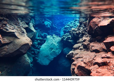 Between two tectonic plates blue fissure with crystal clear glacier water lava formations volcanic transparent cold and clean, colorful rocks and stones in National park Thingvellir, Silfra in Iceland