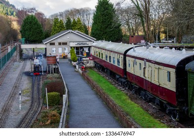 Betws y Coed, UK - Feb 2, 2019: The miniature train of Betws y Coed railway museum operating alongside full size, old carriages.