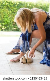 Beuatiful blonde woman with very young golden retriever puppy dog outdoor