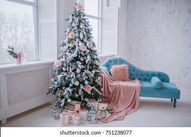 Schöner Weihnachtsbaum reich verziert mit Spielzeug steht vor einem rosafarbenen Stuhl im gemütlichen hellen Raum.