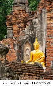Beuatiful golden Buddha Image in front of old pagoda in ancient ruined Buddhist temple in Ayutthya, Thailand